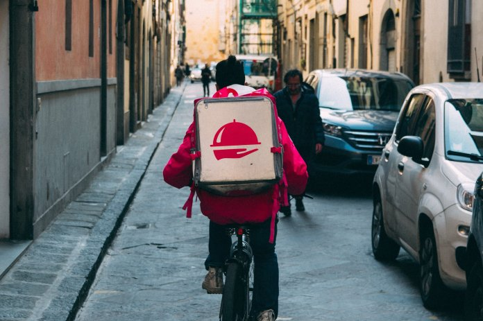 A photo of a man on a bike delivering food. Ordering delivery is a great way to to support local restaurants during this crisis.  Photo by    Kai Pilger    on    Unsplash