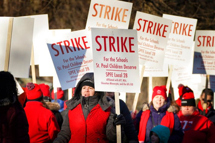 In this March 10, 2020 file photo, St Paul teachers picket outside Adams Elementary in St. Paul, Minn. he union, which represents about 3,600 teachers and support staff, said it was in the best interest of all involved to settle the contract, given the uncertainty of possible school closures due to the coronavirus.  Photo by Glen Stubbe/Star Tribune via AP