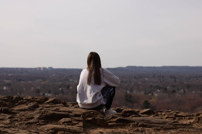 A Newington, Connecticut looks out at the town at the peak of the Cedar Mountain Hiking Trail. Social distancing has meant more time spent out in nature for many residents.  Photo by Kimberly Nguyen/The Daily Campus