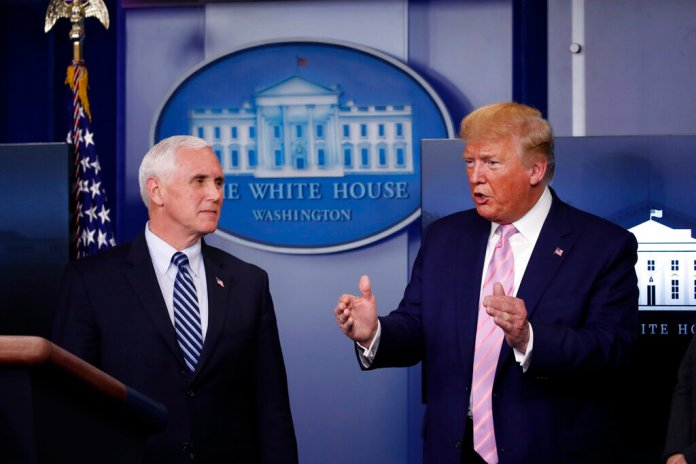 President Donald Trump speaks about the coronavirus in the James Brady Press Briefing Room of the White House, Wednesday, in Washington, as Vice President Mike Pence listens.  Photo by Alex Brandon/AP