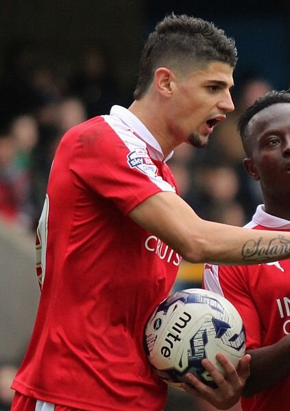 Raphael Rossi-Branco of Swindon Town and Lee Gregory of Millwall push at each other.  Photo in the    public domain