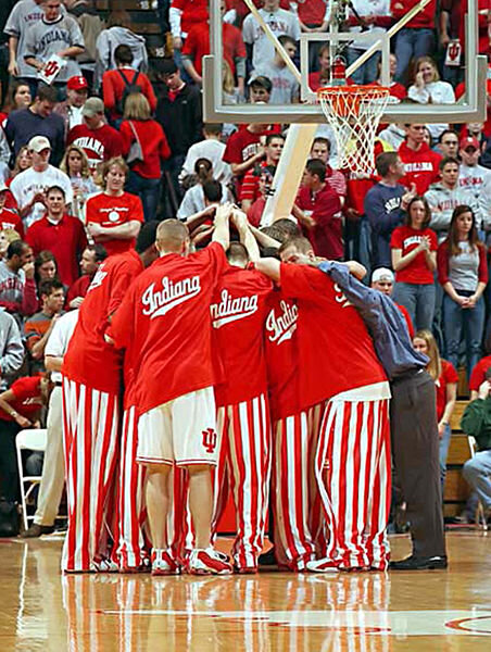 """This is a photo of the Indiana University men's basketball team in a huddle before their home game on January 15, 2003. Players are shown wearing their iconic candy striped pants and classic warm-ups with cursive """"Indiana"""".  Photo in the    public domain"""