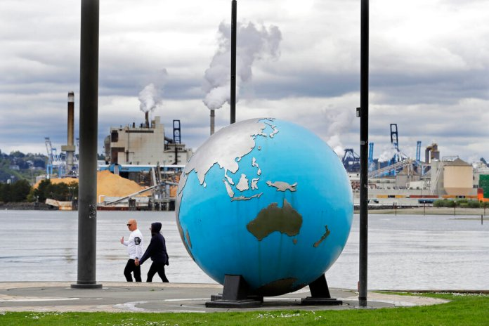 People walk past an Earth globe sculpture at Thea's Park in Tacoma, Wash., with the WestRock Paper Mill in the background. Wednesday is the 50th anniversary of Earth Day, and observance that helped spur activism against air and water pollution and disappearing plants and animals, but ongoing challenges remain throughout the world. Photo by Ted S. Warren/AP