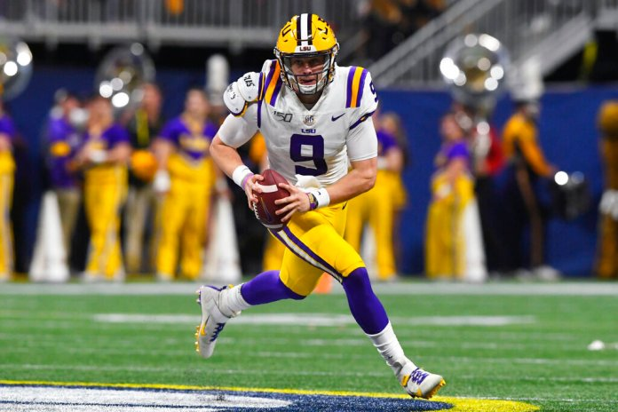 LSU quarterback Joe Burrow runs down field against Georgia during the first half of the Southeastern Conference championship game in Atlanta. Burrow is expected to be a first round pick at the NFL Draft on Thursday.  Photo by John Amis/AP