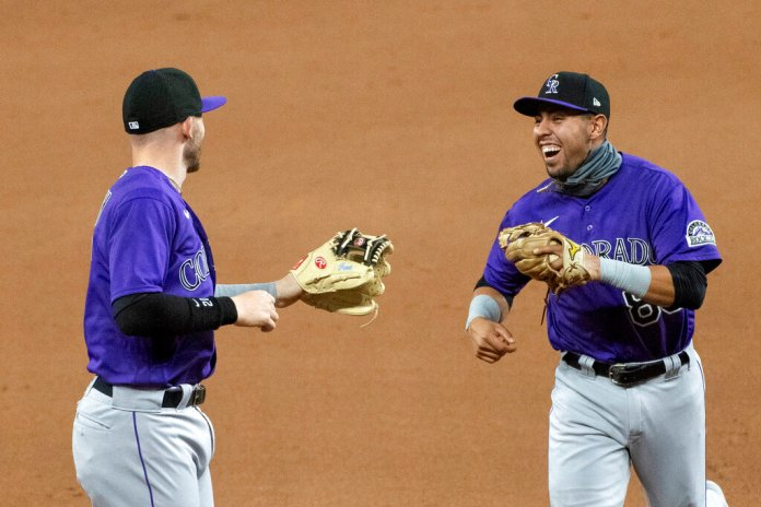 Colorado Rockies second baseman Alan Trejo, right, and shortstop Trevor Story celebrate an inning-ending fielder's choice against the Texas Rangers in the seventh inning of a baseball game Wednesday, July 22, 2020, in Arlington, Texas. Colorado won 7-3.  Photo by Jeffrey McWhorter/AP