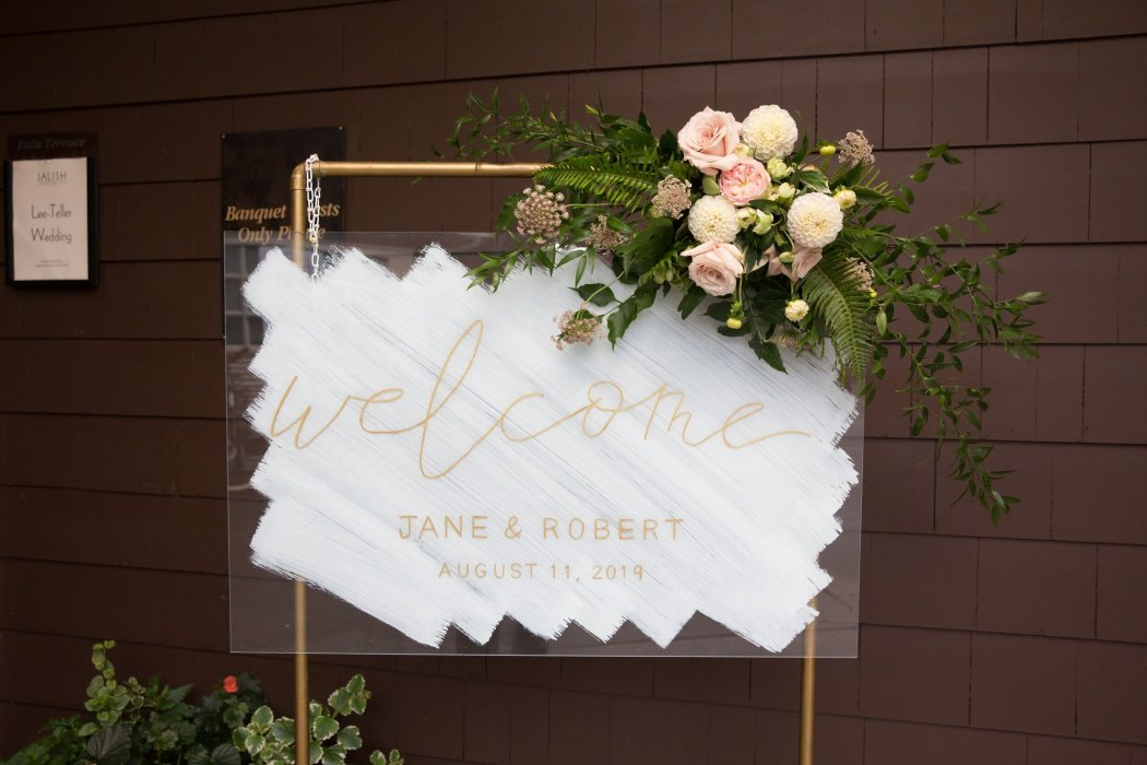 A great way to feature your wedding colors on your wedding signage is to feature them on an acrylic sign like featured here with a painted splash of cream behind gold hand lettering. Jean-Marcus Strole Photography