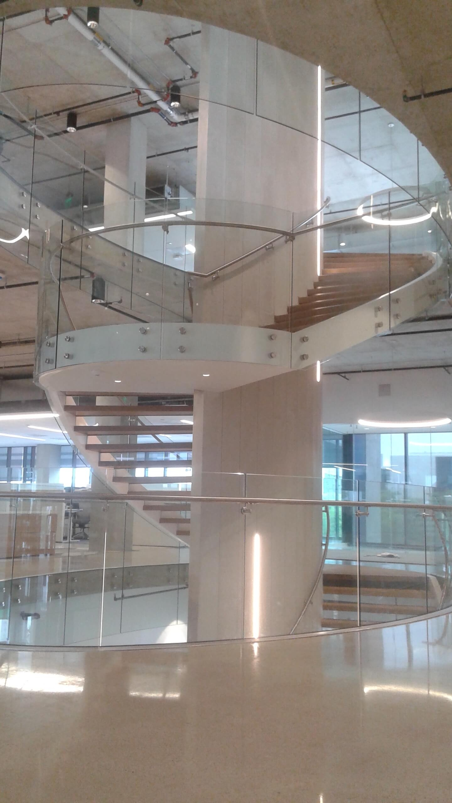 From The Field Curved Glass Point Supported Spiral Staircase | Curved Glass Stair Railing | Residential Glass | Commercial Glass | Band Glass | Walnut | Frameless Glass