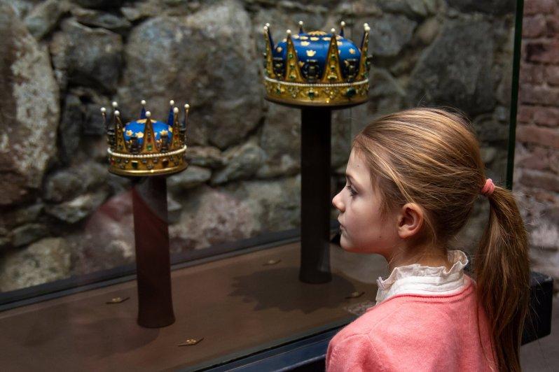 Ein wenig eingeschüchtert schaut sich Prinzessin Estelle die Kronen von Prinzessin Hedvig Elisabet Charlotte und von Prinz Fredrik Adolf (r.) an.  ©Henrik Garlöv/Kungl. Hovstaterna