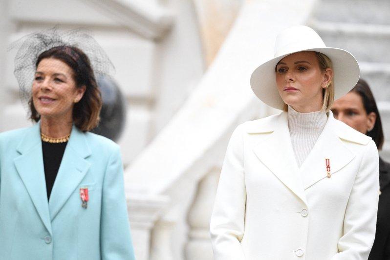 Prinzessin Caroline strahlt im hellblauen Mantel, Fürstin Charlène zeigt sich mit ernster Miene.  © picture alliance / abaca