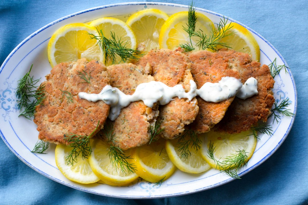salmon cakes on platter with lemon dill sauce, lemon slices and dill on blue napkin