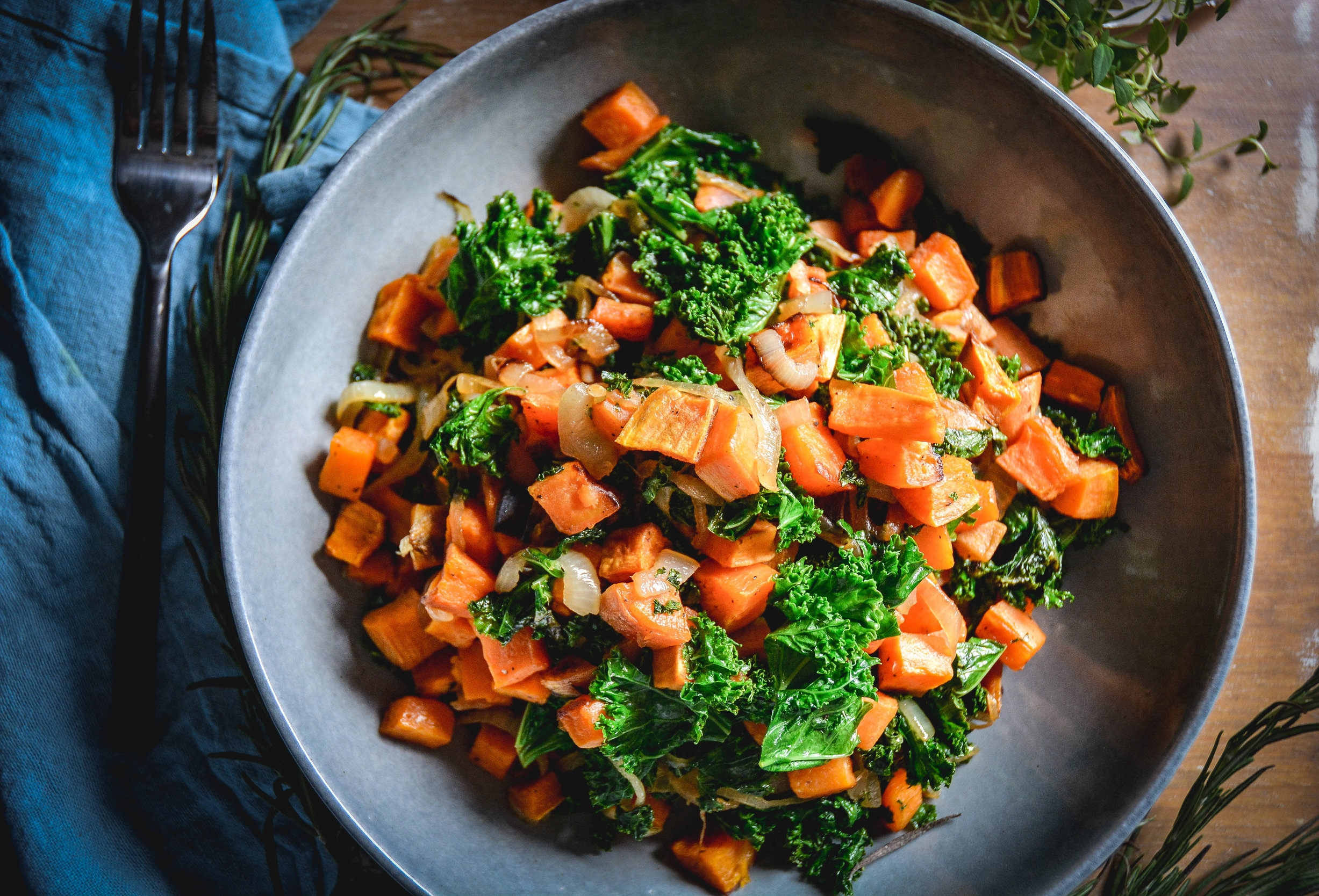 sweet potatoes in bowl with kale, blue napkin and fork