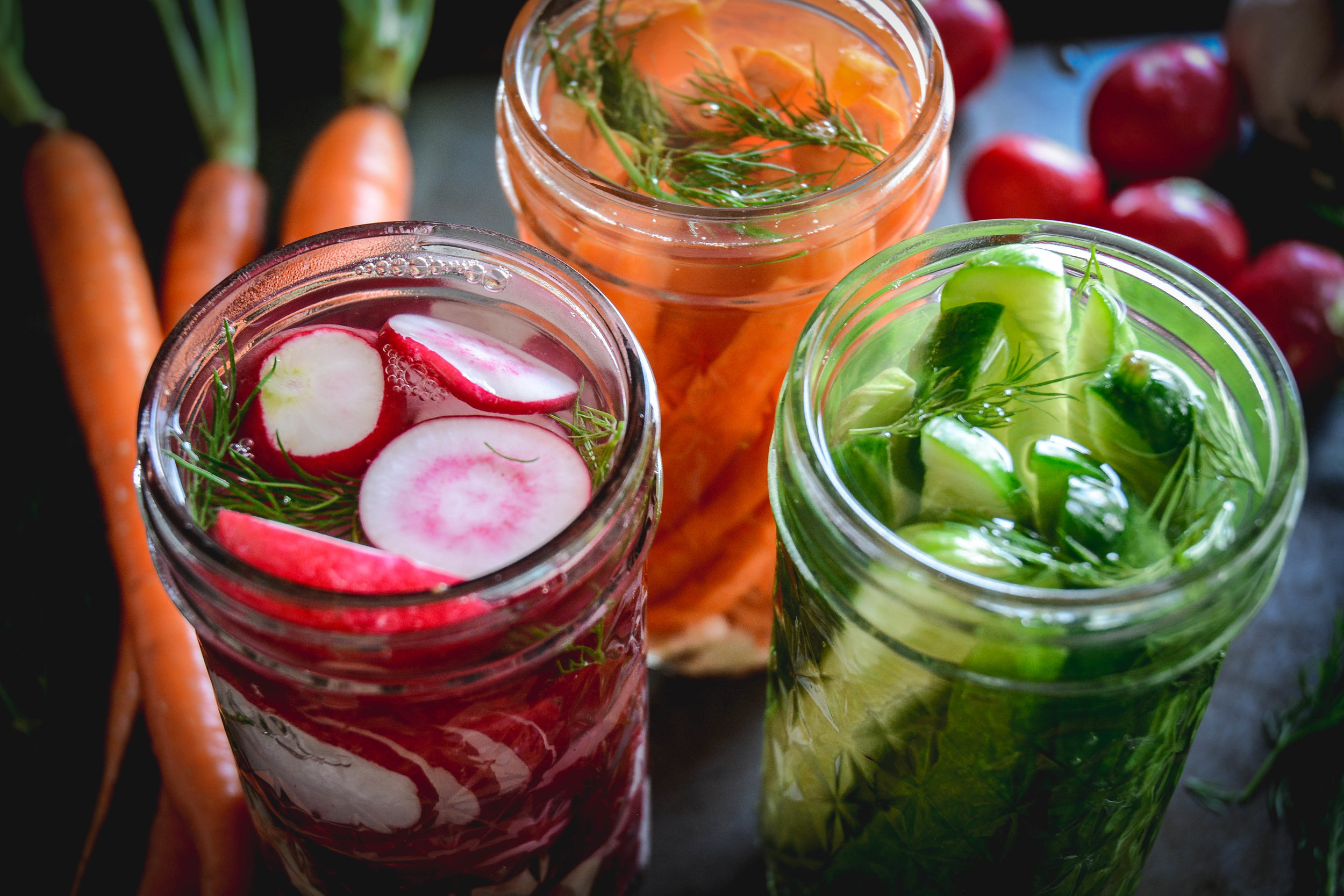 sideways view of cucumbers, sliced radishes and carrot sticks in jars