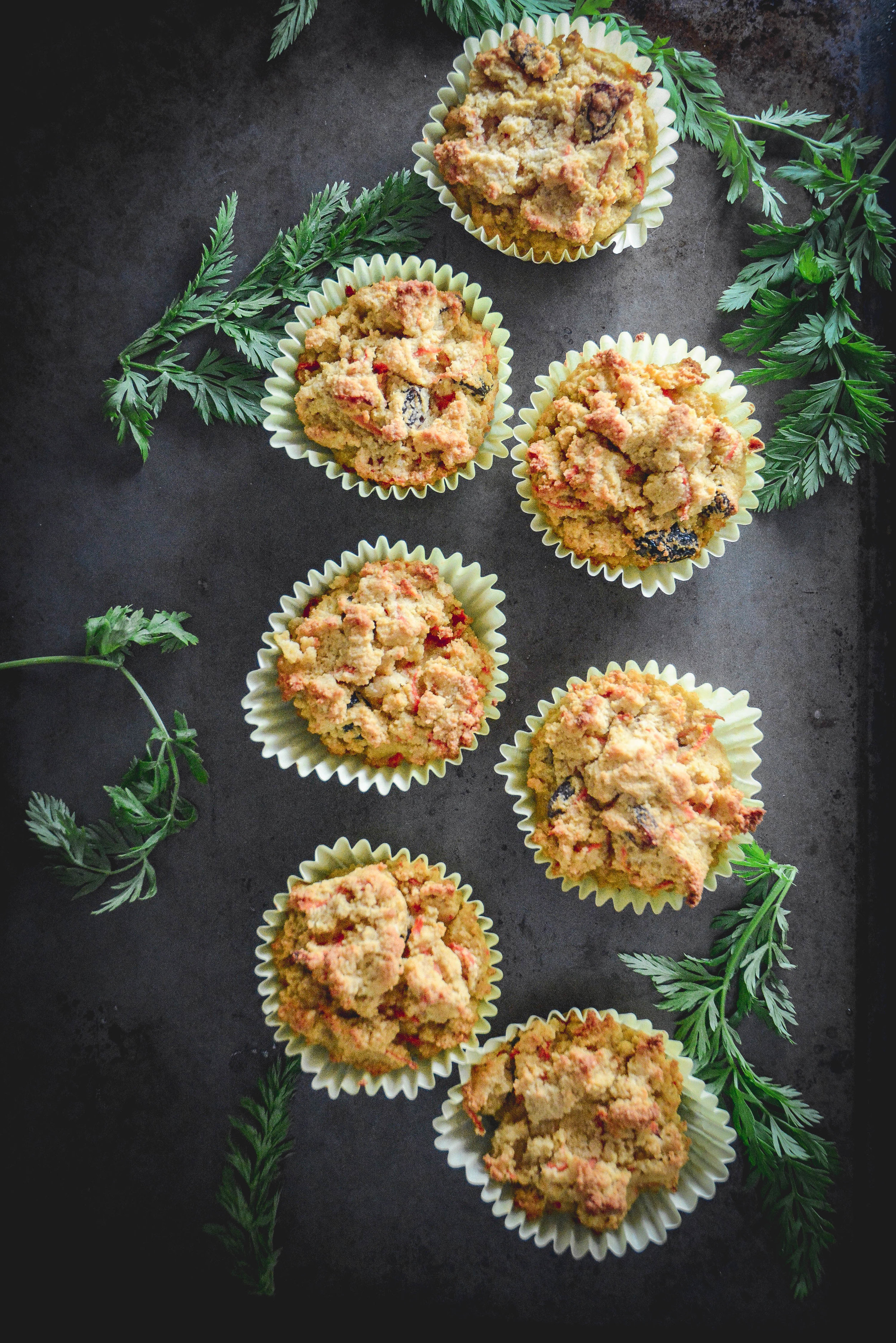 paleo cardamom carrot muffins on dark tray with greens
