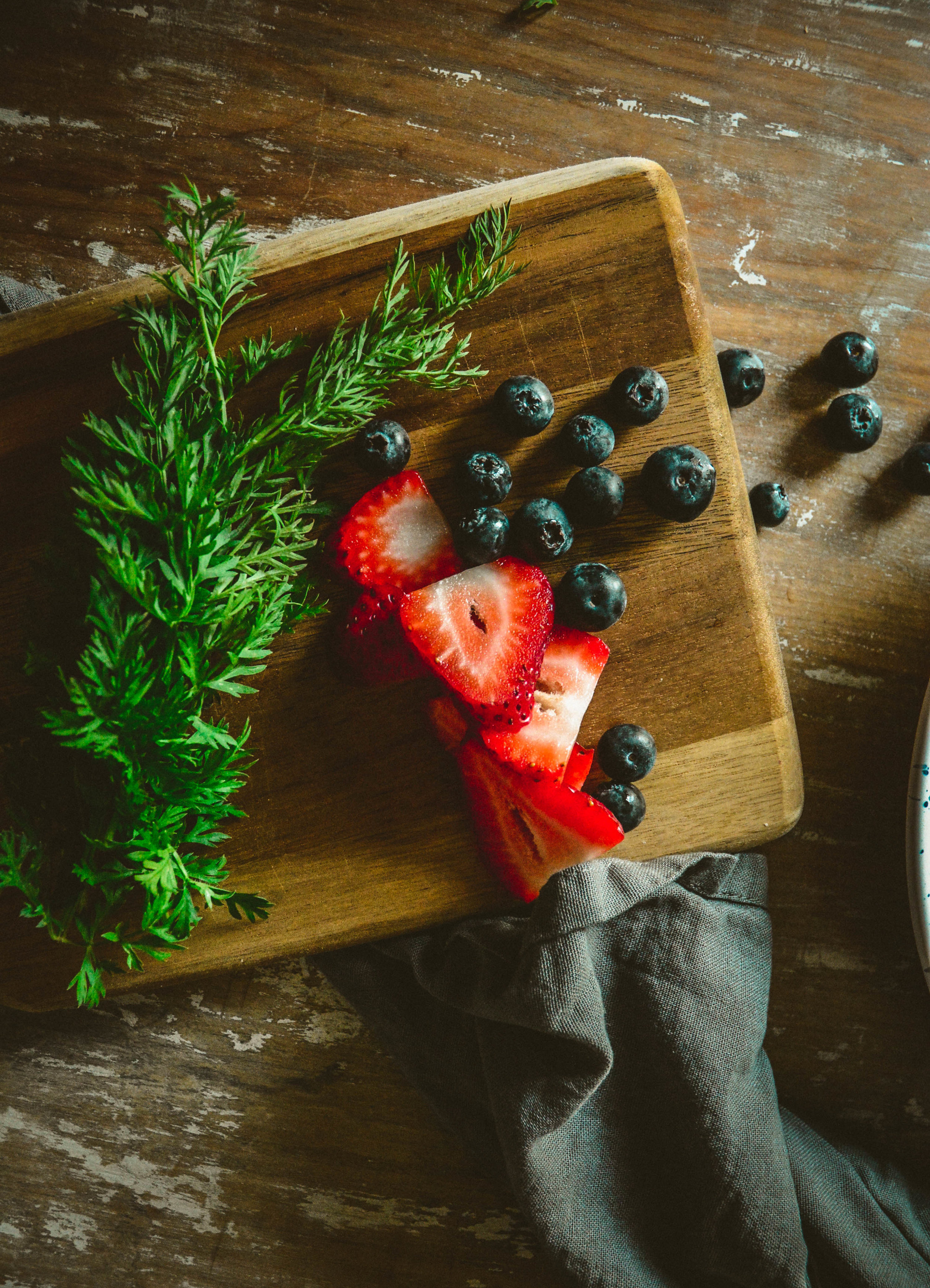 Strawberries, blueberries and greens on cutting board