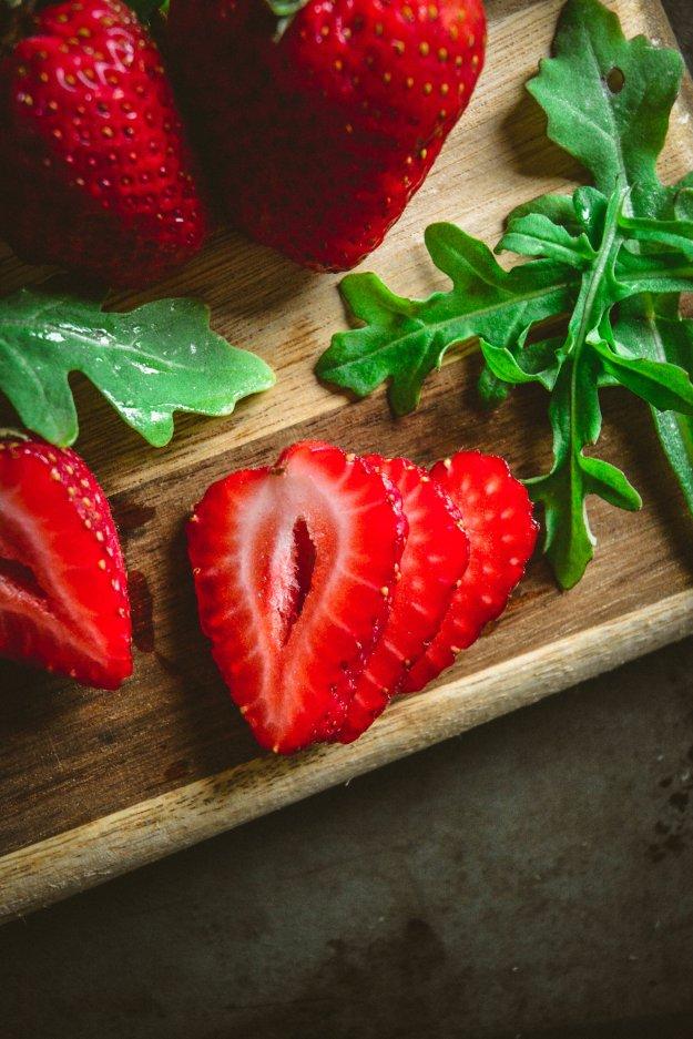 strawberries and arugula on cutting board