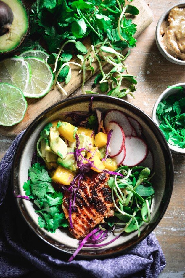 paleo fish taco bowl with mango salsa, cilantro and radish slices in bowl