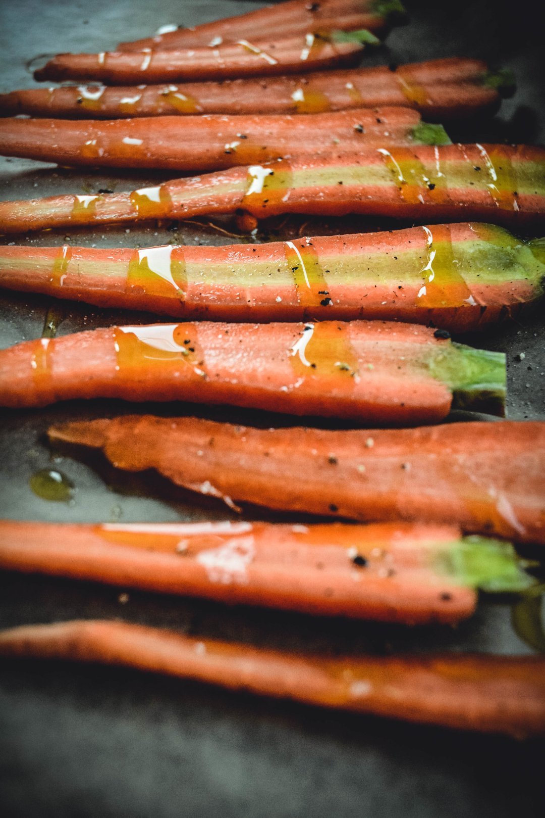 carrots sliced on tray drizzled with olive oil