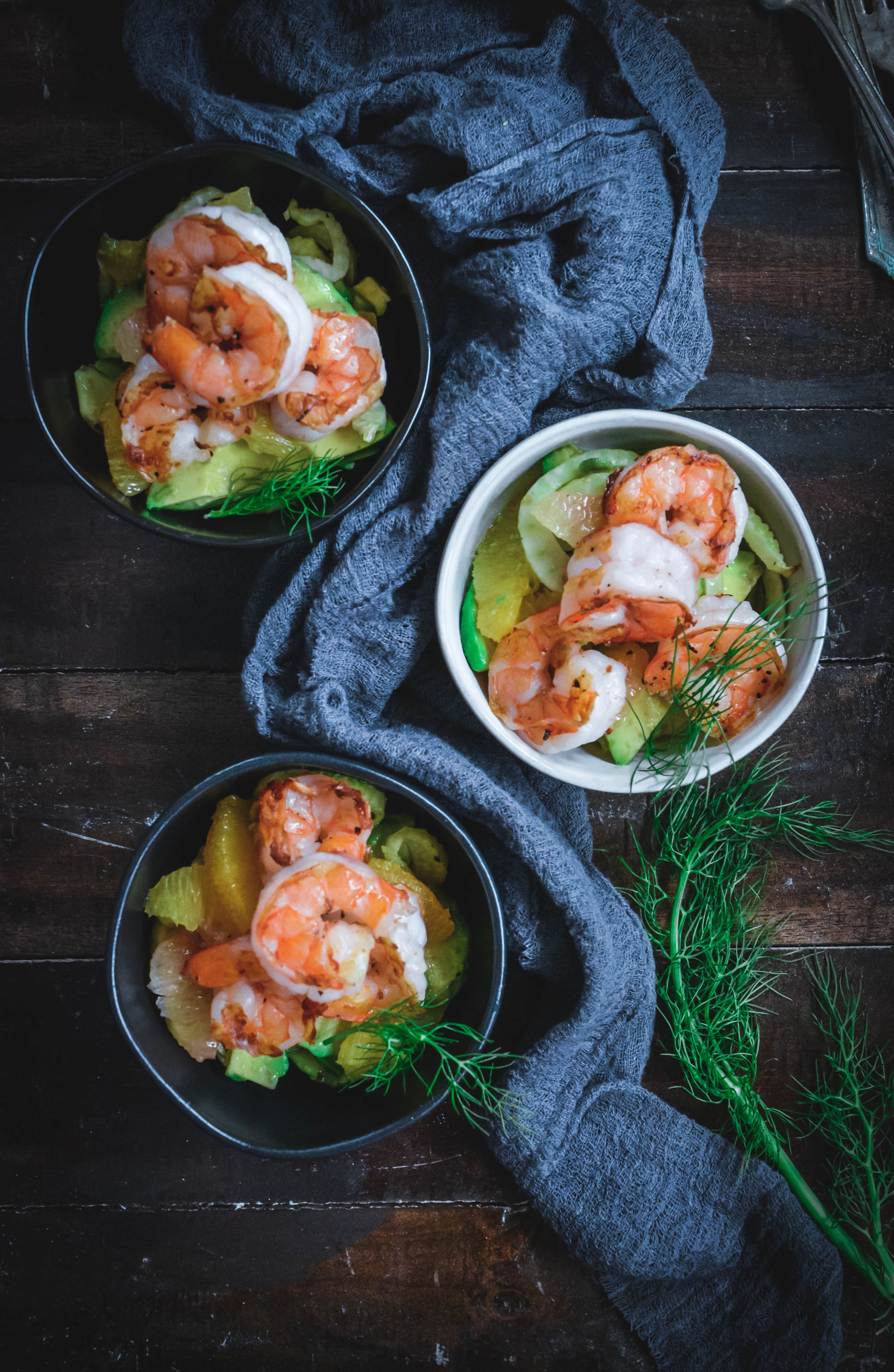 Shrimp Salad with Fennel, Citrus and Avocado in bowls with dill and napkin