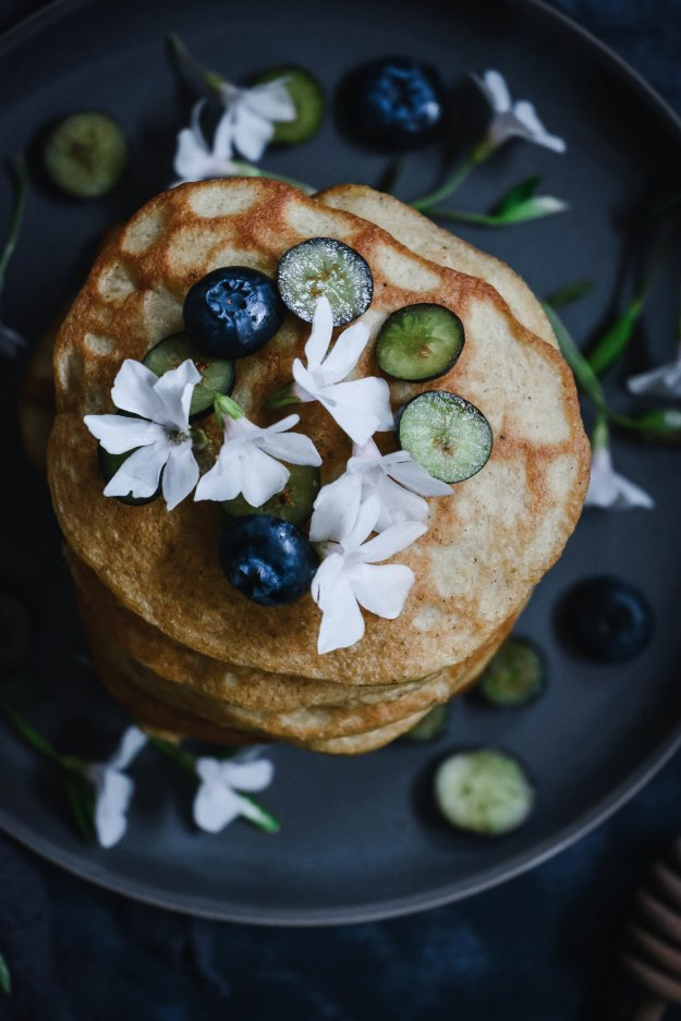 pancakes stacked and topped with flowers and blueberries