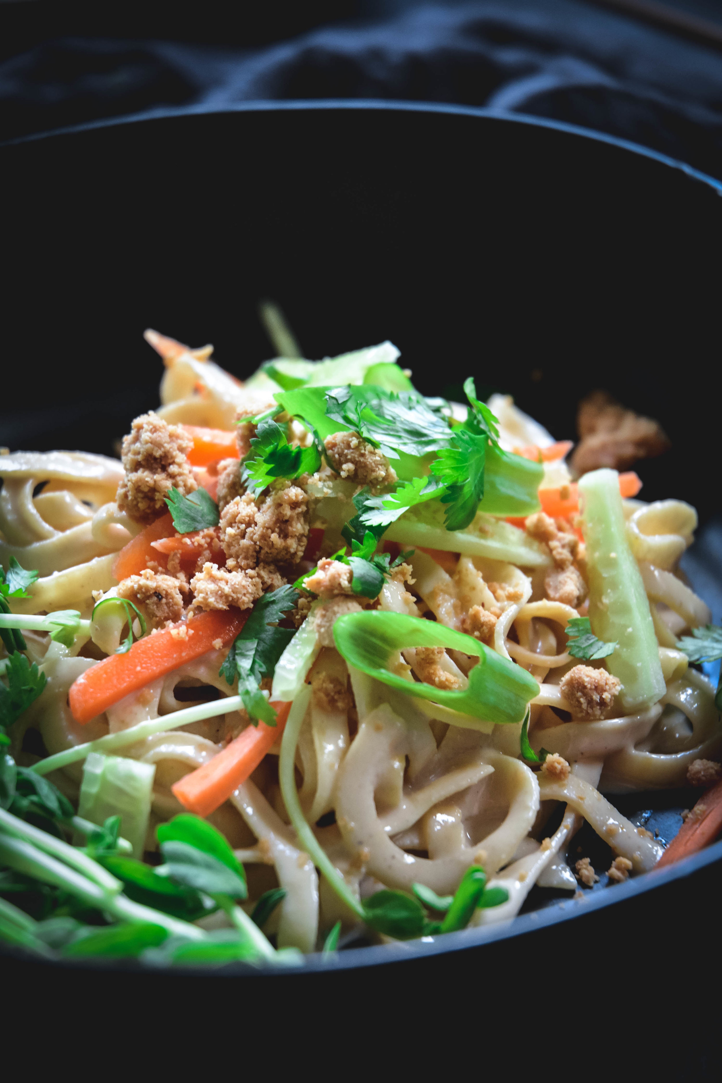 Rutabaga noodles in bowl with casew crumble, cilantro and scallions, carrots