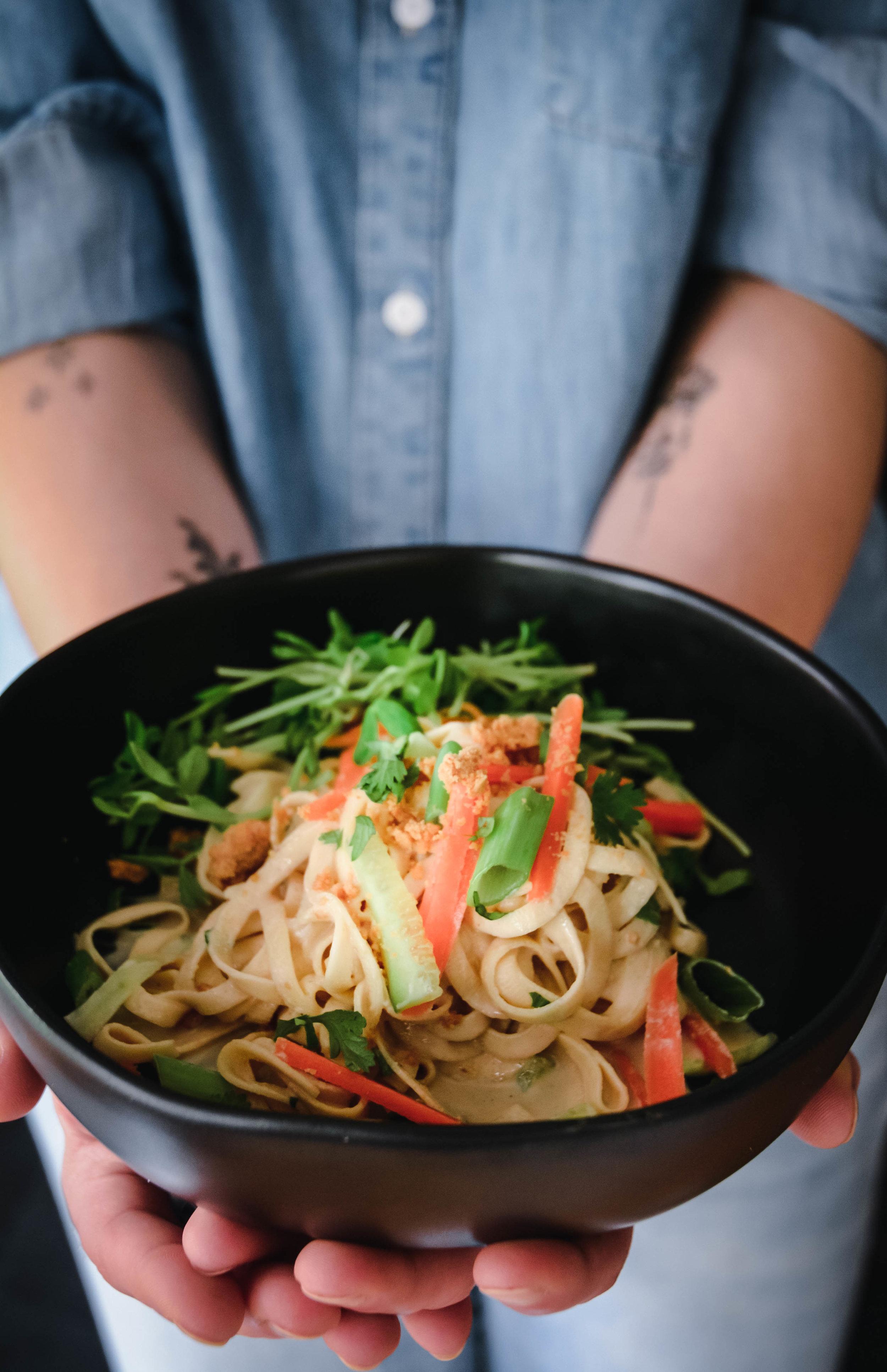 Hands holding bowl of rutabga noodles