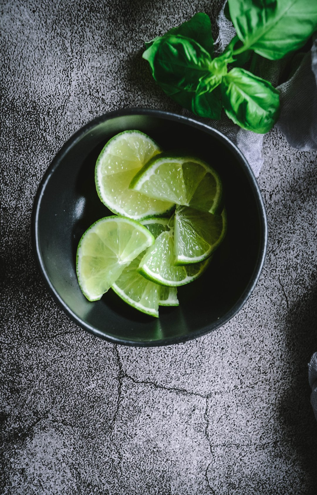 bowl of lime slices and basil