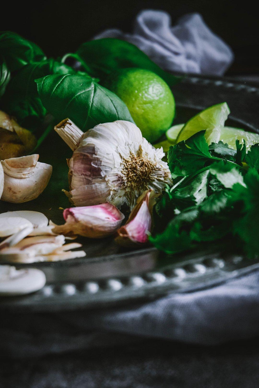 Garlic, basil and limes on plate
