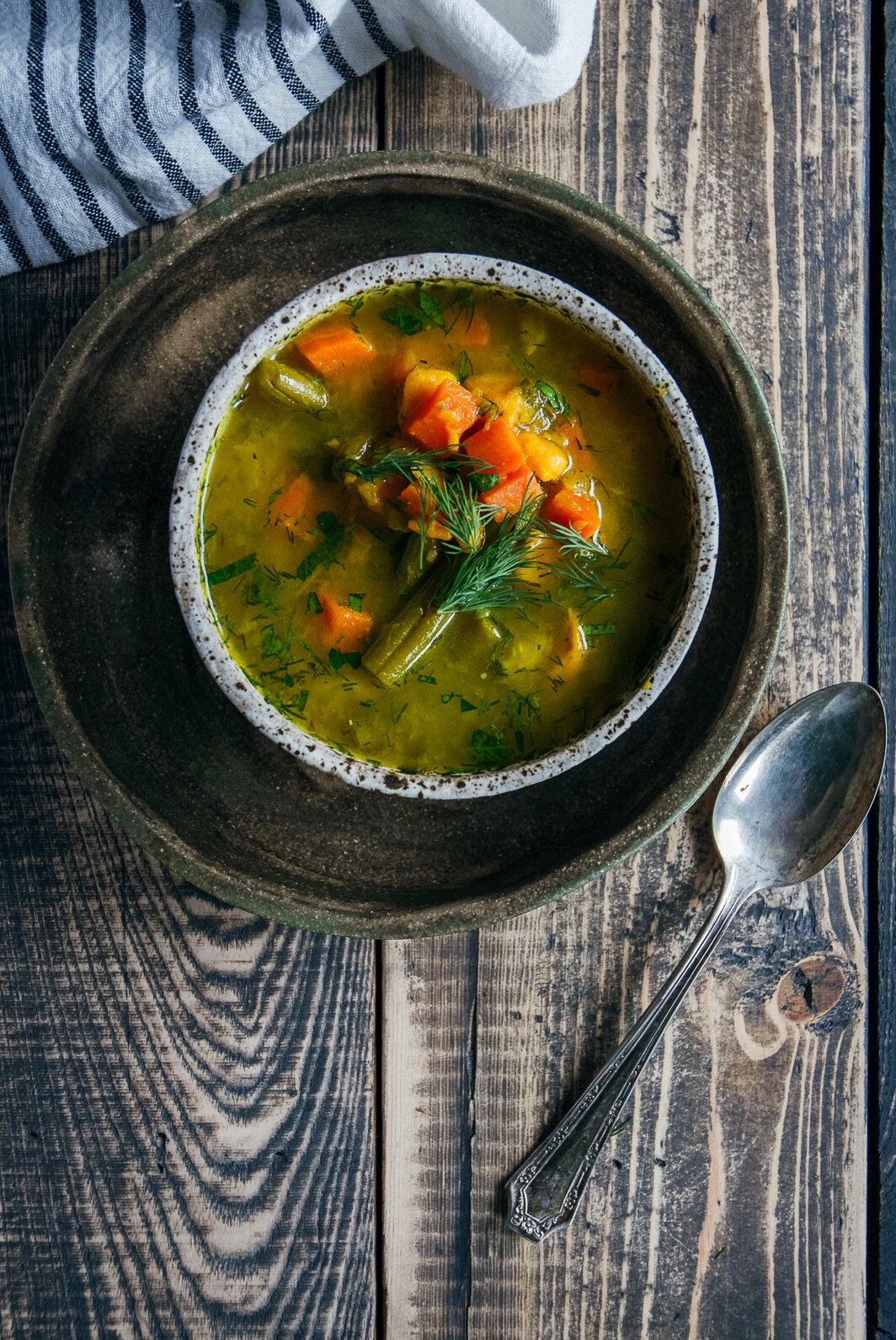 bone broth vegetable soup in bowl on plate with napkin and spoon