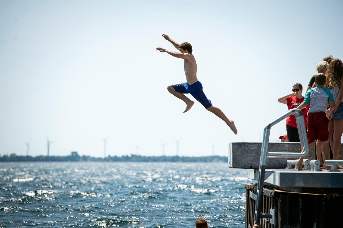 Leaping into Lake Ontario from the Gord Edgar Downie pier in Kingston, Ontario.
