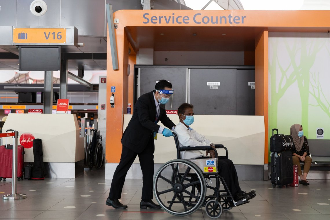 Photo caption: A Guest Service Agent assisting to transport a guest on a wheelchair.
