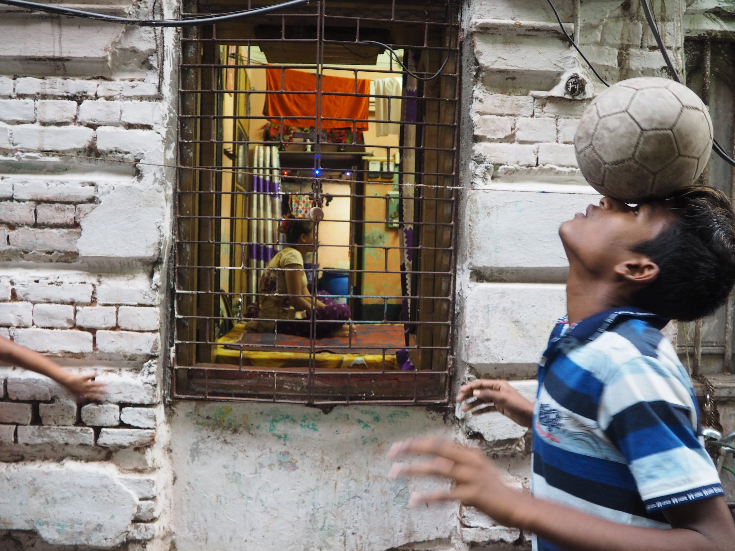 A Durbar footballer practices in an alleyway of Sonagachi while a sex worker looks on.