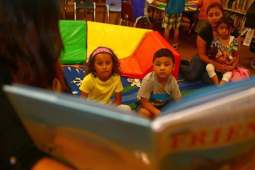 Kids are never too old to share a good book with their families. Lance Cpl. Christopher Johns, Marine Corps Air Station, Miramar, CA. Public domain, via Wikimedia Commons