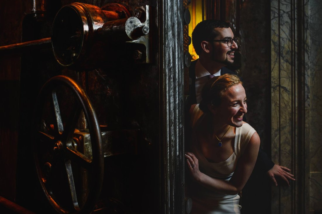 man and woman smiling and peeking out from behind vault door