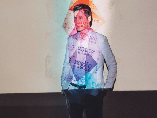 man in a gray suit with colorful shapes and text projected on him
