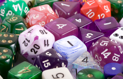 Pictured: Several polyhedral dice of various shapes in deep shades of purple, blue and green. Picture Source: canva.com
