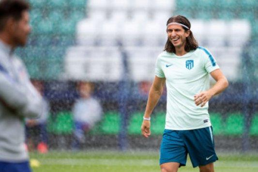 14 August 2018, Estonia, Tallinn: soccer, UEFA Super Cup, Training Atletico Madrid at Lillekula Stadium. Player Filipe Luis (R) laughs as he approaches the sprinkler training.…