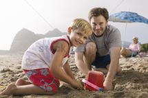 Father Building Sandcastle With Son Beach Stock