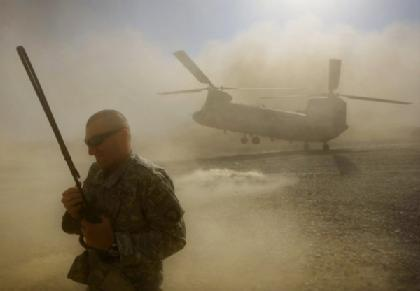 Dust and debris engulf a US Army soldier as a Chinook supply helicopter lands in Khost province along the Afghanistan-Pakistan border.