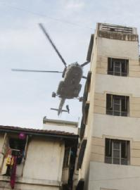 Commandoes get down from a chopper to the roof of a house owned by Israelis in Colaba, Mumbai.