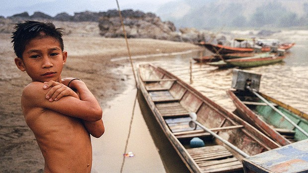 A boy stands on the banks of the Mekong River near the relocation site for a Lao village, which was moved to make way for the Xayaburi Dam.