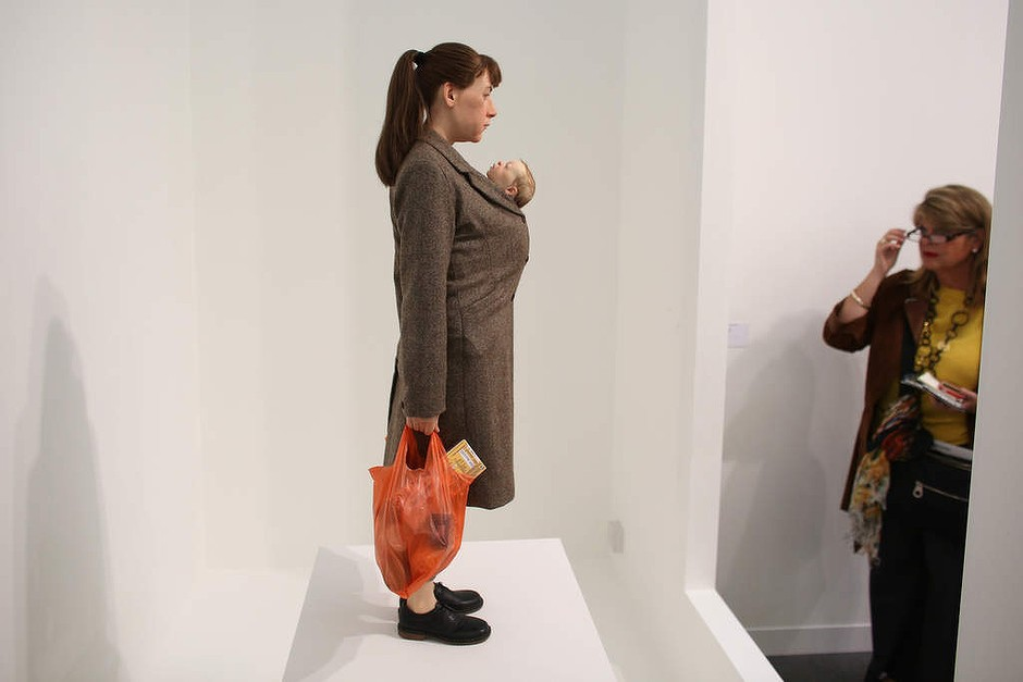 A woman views Ron Mueck's artwork 'Woman with Shopping' at the Frieze London art fair.