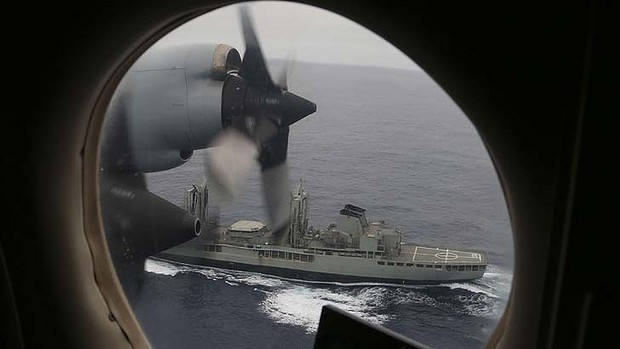 A Royal Australian Air Force AP-3C Orion flies past  HMAS Success as they search for missing Malaysia Airlines flight MH370  in the southern Indian Ocean on March 22, 2014.