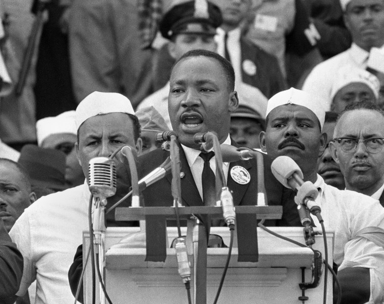 Black and white photo of a suited Martin Luther King Jr. behind a plethora of microphones and surrounded by ethnic minorities in America