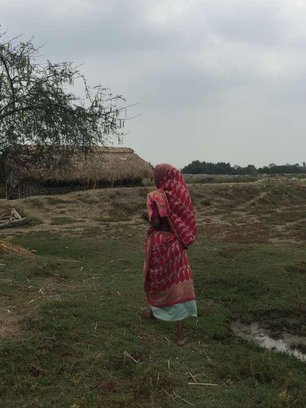 A woman dressed in a pink sari walks across a field.
