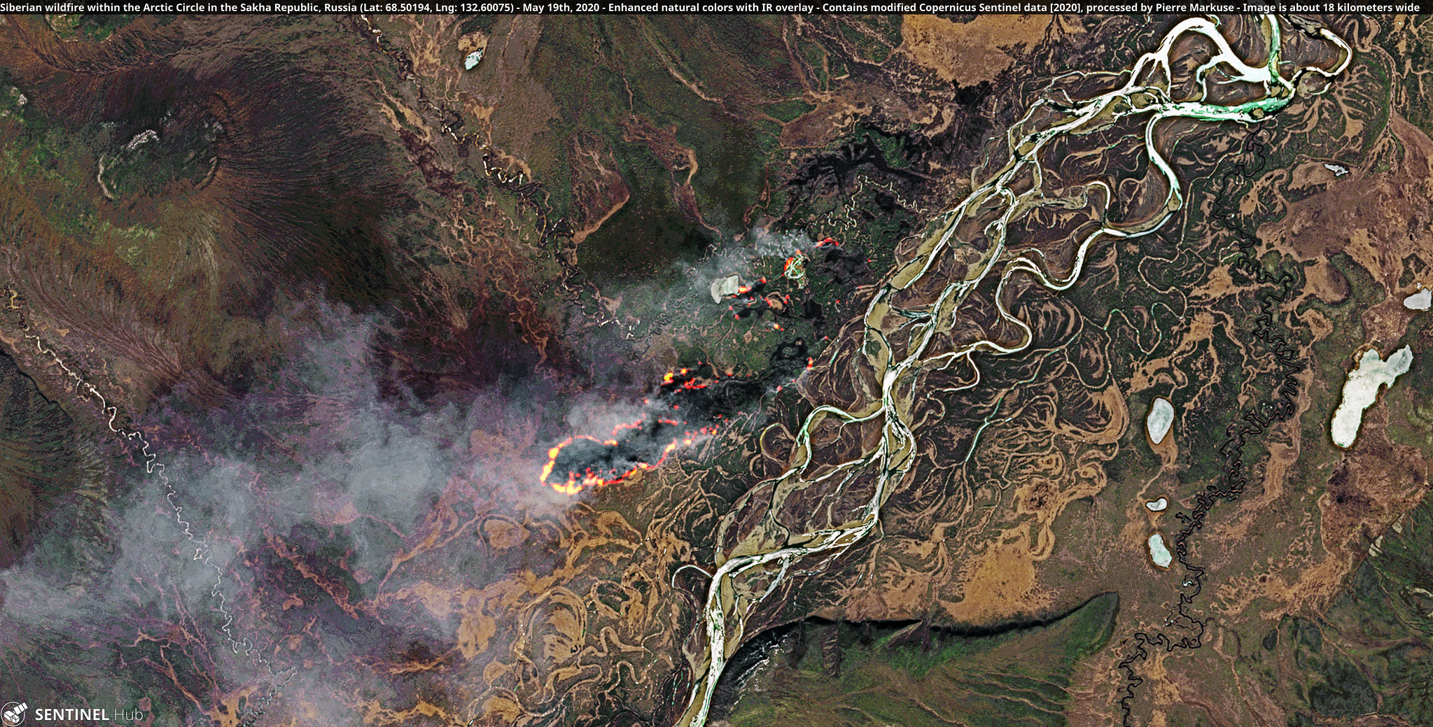 A full-colour satellite image of multiple fires burning in a forested river valley