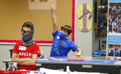 Two boys in a classroom wearing masks, with one raising his hand.