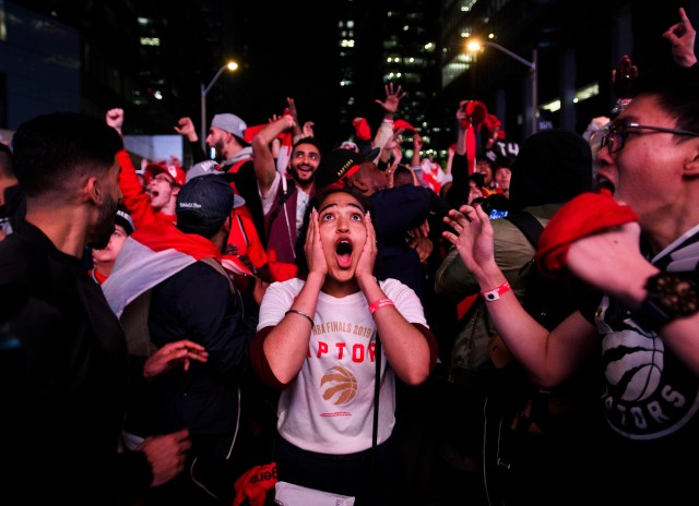 Fans cheer and celebrate the Toronto Raptors victory outdoors at night.