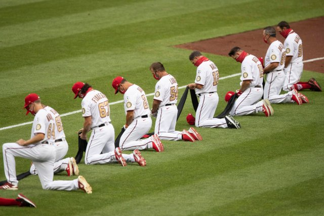 A row of baseball players, each holding the same long strip of black cloth, kneel.