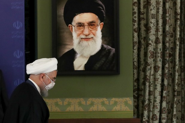 Iranian President Hassan Rouhani walking in front of a portrait of Supreme Leader Ayatollah Ali Khamenei