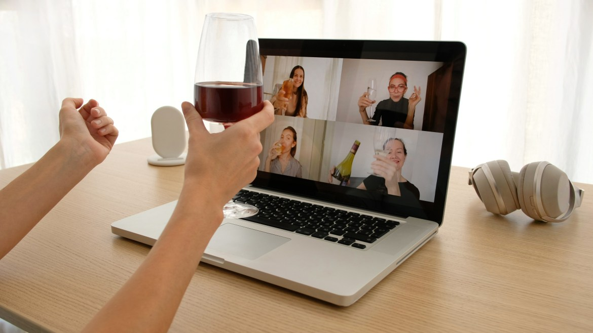 Woman drinks wine in front of laptop showing video call.
